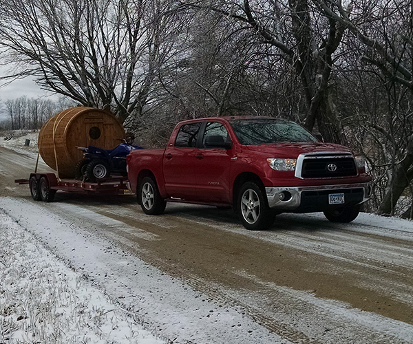 RW Saunas Delivering Sauna with red truck and trailer